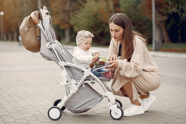 캐리지가 공원에서 산책하는 젊은 어머니
