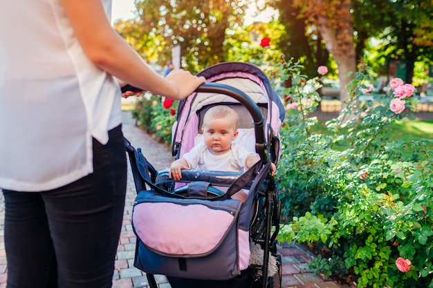 Young mother walking in park with baby girl in carriage.