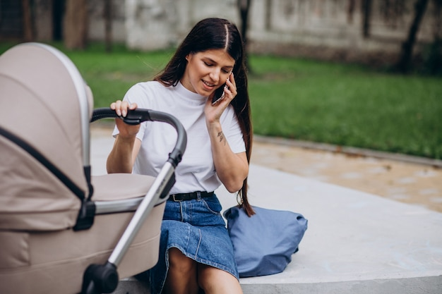 Young mother walking in park with baby stroller and talking on phone