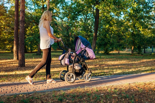 Young mother walking in summer park with baby carriage.