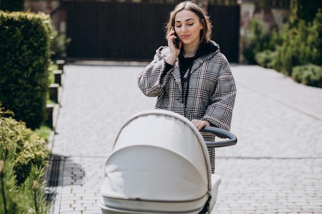 젊은 어머니는 공원에서 유모차와 함께 산책과 전화 통화
