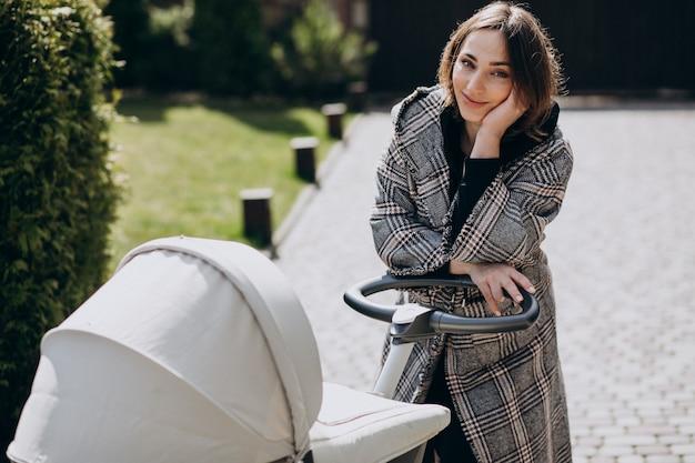 Молодая мать гуляет с коляской в парке