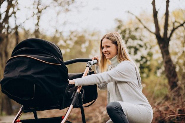 公園でベビーカーで歩く若い母親