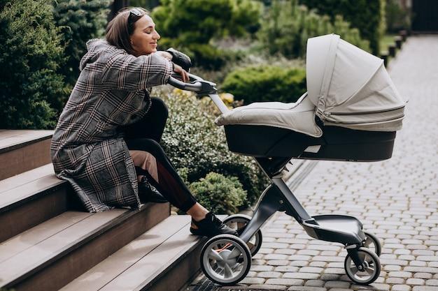 Молодая мама гуляет с коляской на заднем дворе