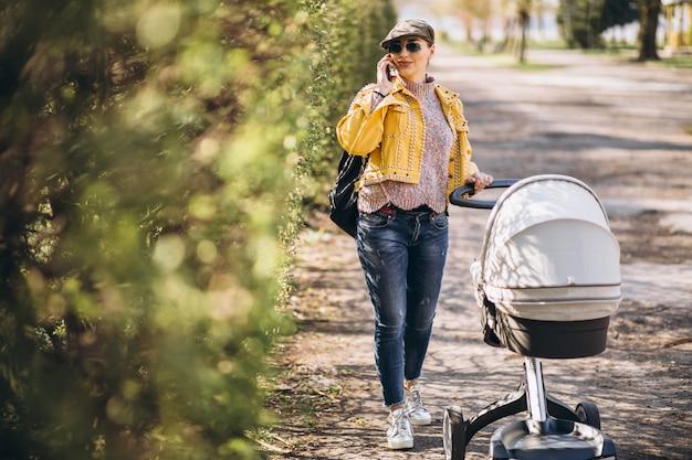 Giovane madre che cammina con carrozzina nel parco e utilizzando il telefono
