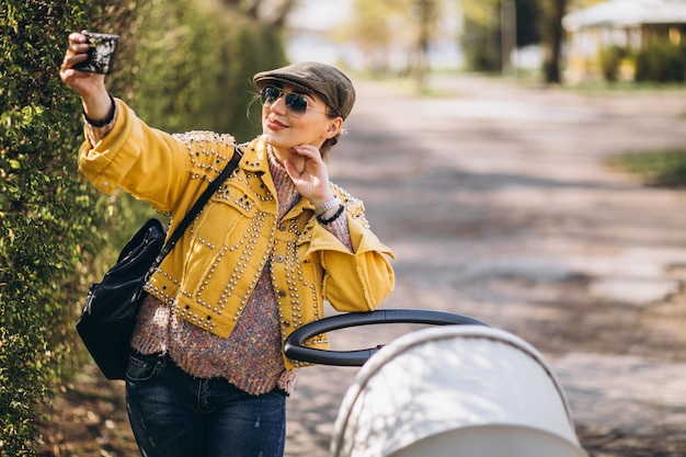 Young mother walking with baby carriage in park and using phone