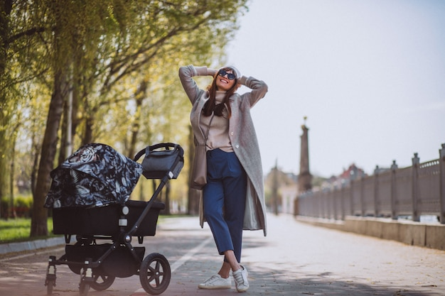 Young mother walking with baby carriage in park