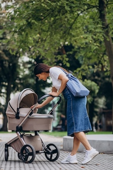 Young mother walking with baby stroller in park