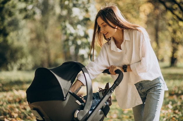 Молодая мать гуляет с детской коляской