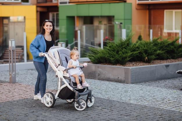 赤ちゃんと一緒に歩いている若い母親は、美しい乳母車でそれを運びます。幸せ。