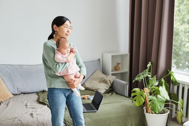 방 주위에 그녀의 아기와 함께 걷는 젊은 어머니