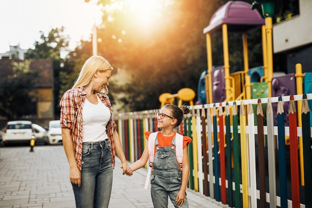 Young mother walking with her little daughter to elementary school. back to school concept.