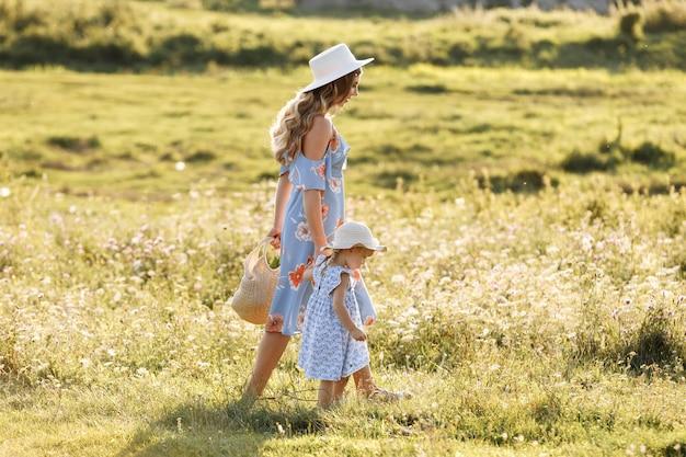 그린 필드에서 작은 딸과 함께 산책 젊은 어머니.