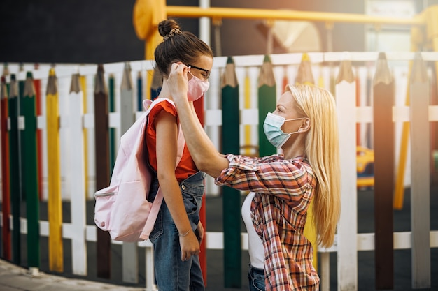 街の通りを彼女の小さな娘と一緒に歩いている若い母親。彼らは顔面保護マスクを着用しています。学校に戻って、新しいコロナウイルスのライフスタイルの概念。