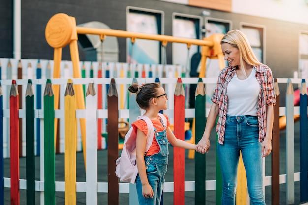 어린 딸과 함께 초등학교에 가는 젊은 어머니. 학교 개념으로 돌아가기.