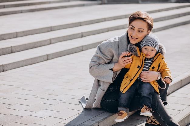公園で彼女の小さな幼児の息子と一緒に歩いている若い母親