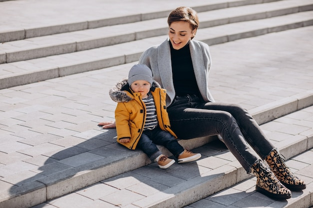 Young mother walking with her little toddler son in park