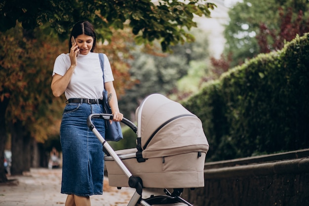 Young mother walking with stroller in park and talking on the phone