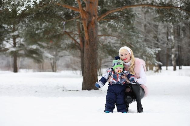 Young mother walks on a winter day with a baby in her arms in the park