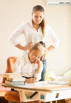 Молодая мать смотрит на дочь, делая домашнее задание