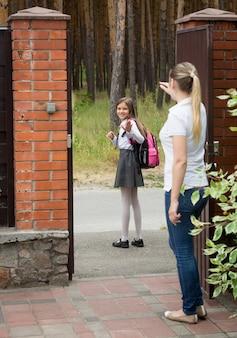 学校を歩いている娘に手を振っている若い母親