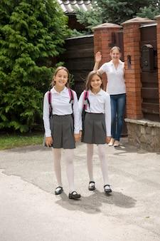 学校に歩いている娘たちに手で手を振っている若い母親