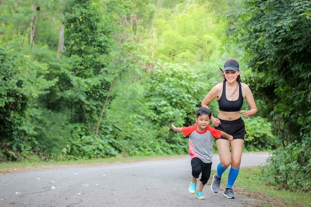 Young mother wear sport cloth and her son boy running at nature outdoor