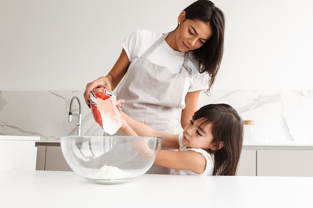 Young mother wearing apron cooking pastry with her little daughter together, in home kitchen