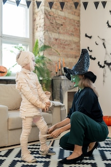 Young mother in witch costume wrapping her son into zombie attire