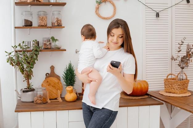 キッチンで白い服を着た赤ちゃんを持つ若い母親は、マグカップから飲み物を調理しますスマートフォンを保持します