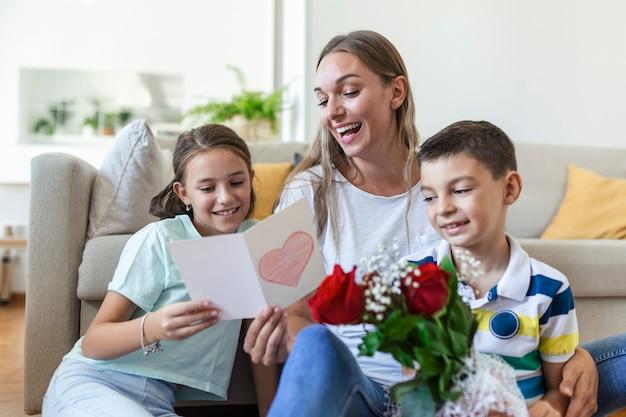 Молодая мама с букетом роз смеется, обнимая сына, а веселая девочка с открыткой и розами поздравляет маму во время празднования праздника на кухне дома.
