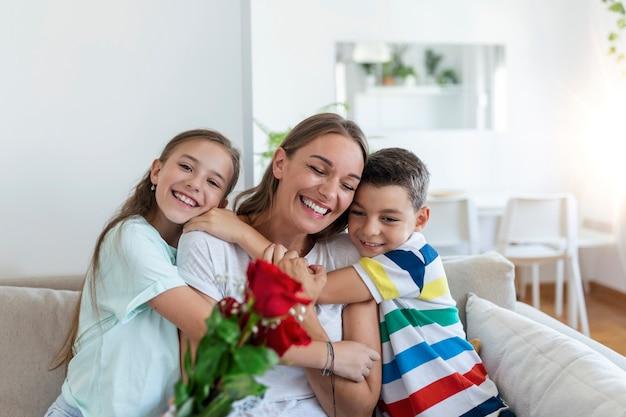 Молодая мама с букетом роз смеется, обнимая сына, а веселая девочка с открыткой поздравляет маму во время празднования праздника на кухне дома.