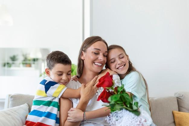 バラの花束を持った若い母親が笑い、息子を抱きしめ、カードを持った陽気な女の子が自宅のキッチンでの休日のお祝い中にお母さんを祝福します