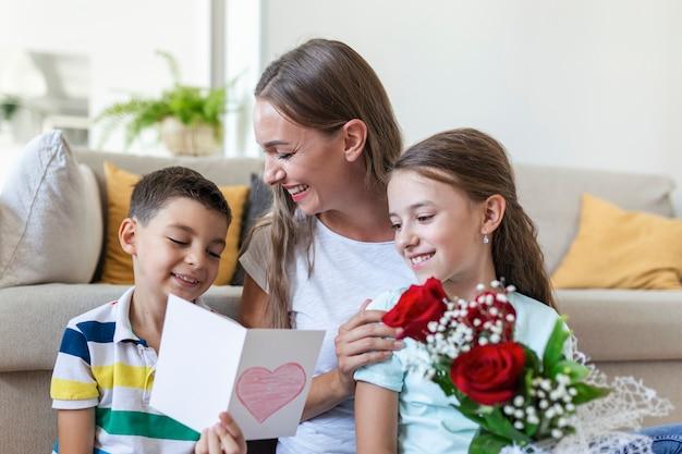 Молодая мама с букетом роз смеется, обнимая сына, а веселая девочка с открыткой и розами поздравляет маму во время празднования праздника дома. день матери