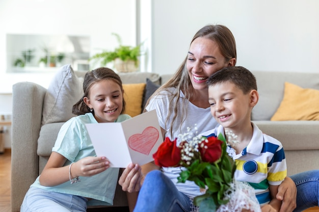 Молодая мама с букетом роз смеется, обнимая сына, а веселая девочка с открыткой и розами поздравляет маму во время празднования праздника на кухне дома. день матери