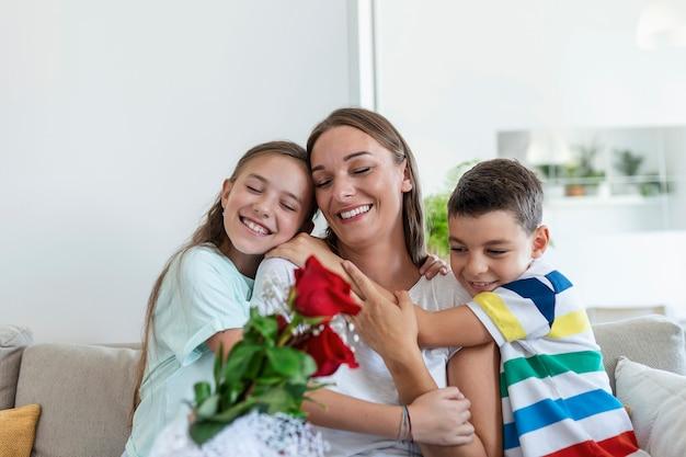 Молодая мама с букетом роз смеется, обнимая сына, а веселая девочка с открыткой поздравляет маму во время празднования праздника на кухне дома