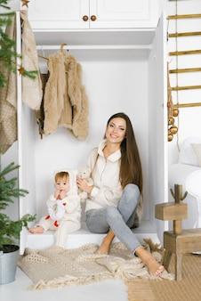 Молодая мама с годовалой дочкой сидит в шкафу