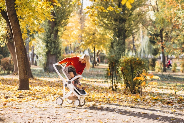 Young mother with baby daughter walking in park in autumn