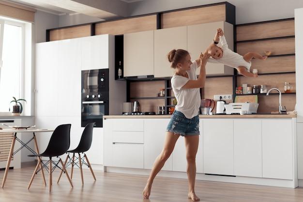 Молодая мама с ребенком весело на кухне дома