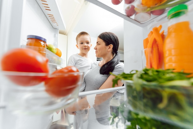 Young mother with baby near open fridge. healthy eating at home concept. vegetables and fruits in the refrigerator