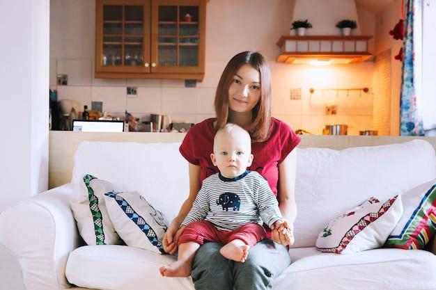家のインテリアのソファに赤ちゃんを持つ若い母親ライフスタイル家族と一体感の概念