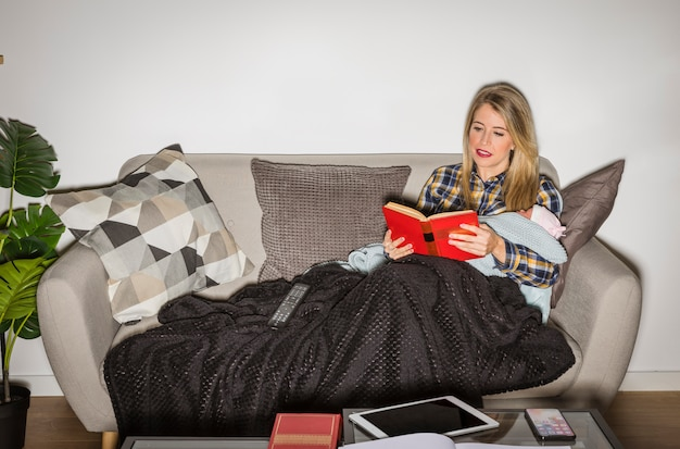 Young mother with baby reading book on couch