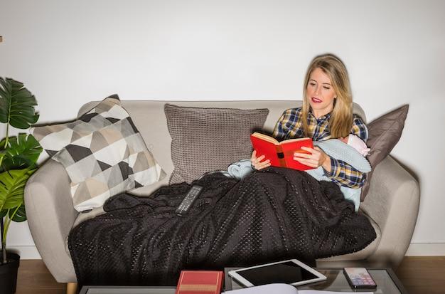 ソファで本を読んで赤ちゃんを持つ若い母親
