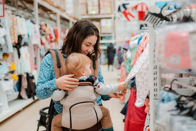 Young mother with baby son shopping in supermarket