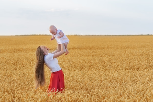 Young mother with beautiful long hair holding cute baby. mom and child playing in wheat field