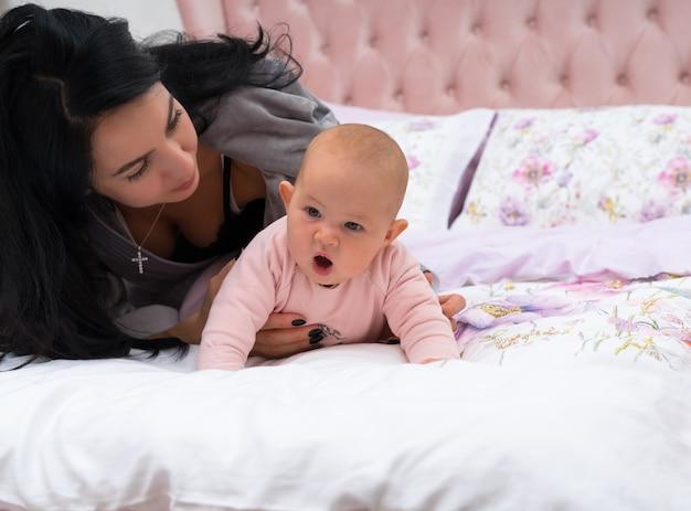 女の子が変な顔でベッドで這うことを試みている間、彼女の小さな赤ちゃんの隣に横たわっている黒い髪の若い母親。コピースペースで正面から見たところ。