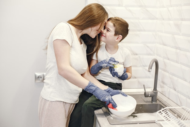 Young mother with a boy washing dishes in the kitchen.