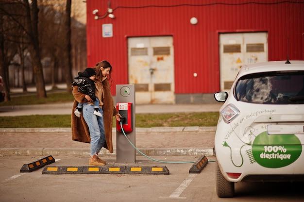 電気ガソリンスタンドで電気自動車を充電する子供を持つ若い母親。