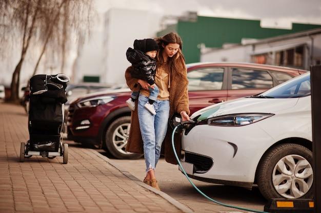 Молодая мать с ребенком, заряжая электромобиль на азс.
