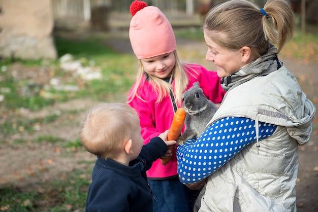 아이들과 함께 젊은 어머니는 농장 마당에서 빵과 당근으로 토끼와 염소에게 먹이를줍니다.